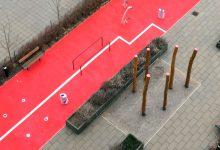 Rød gummibelægning med en hvid stribe igennem. Interaktive redaskaber en gangbare i sort. Stolper med lyserød malet top